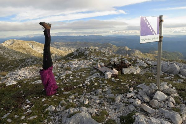 Mountaineer-doing-a-headstand-on-the-summit-of-Mala-Caba-or-'Djoko's-Tower',-Treskavica-mountain,-Bosnia-and-Herzegovina,-photo-by-Elma-Okic_1050x700