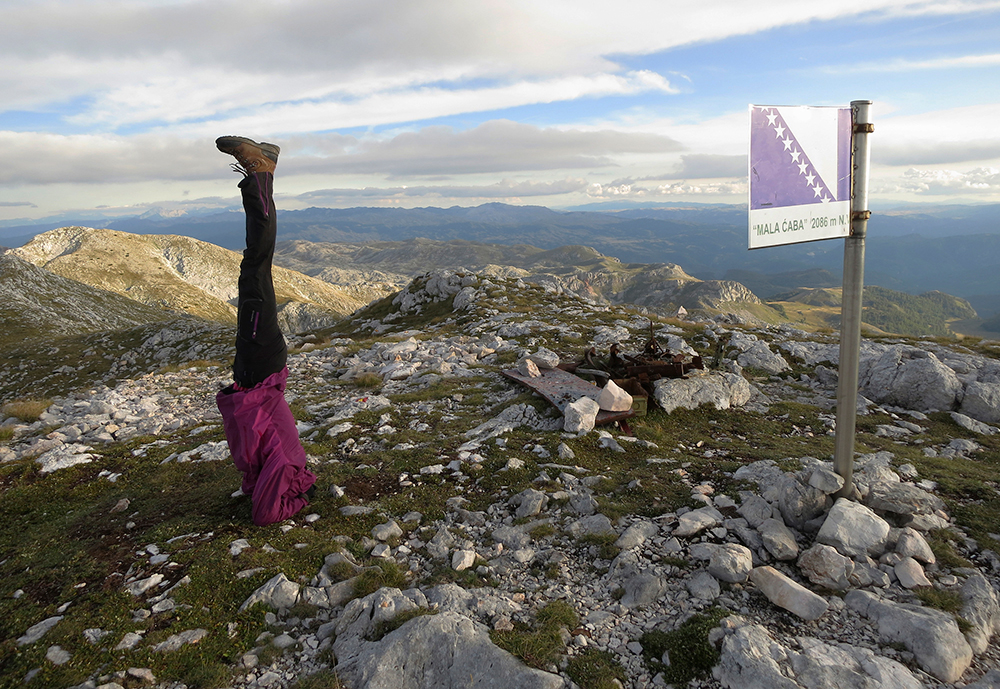 Mountaineer doing a headstand on the summit of Mala Caba or 'Djoko's Tower', Treskavica mountain, Bosnia and Herzegovina, photo by Elma Okic