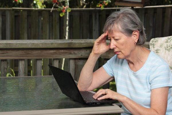 Worried senior woman using laptop.