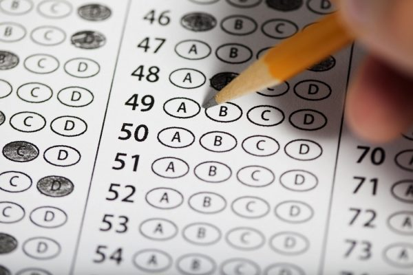 Close of of hand filling out answers on a multiple choice exam.