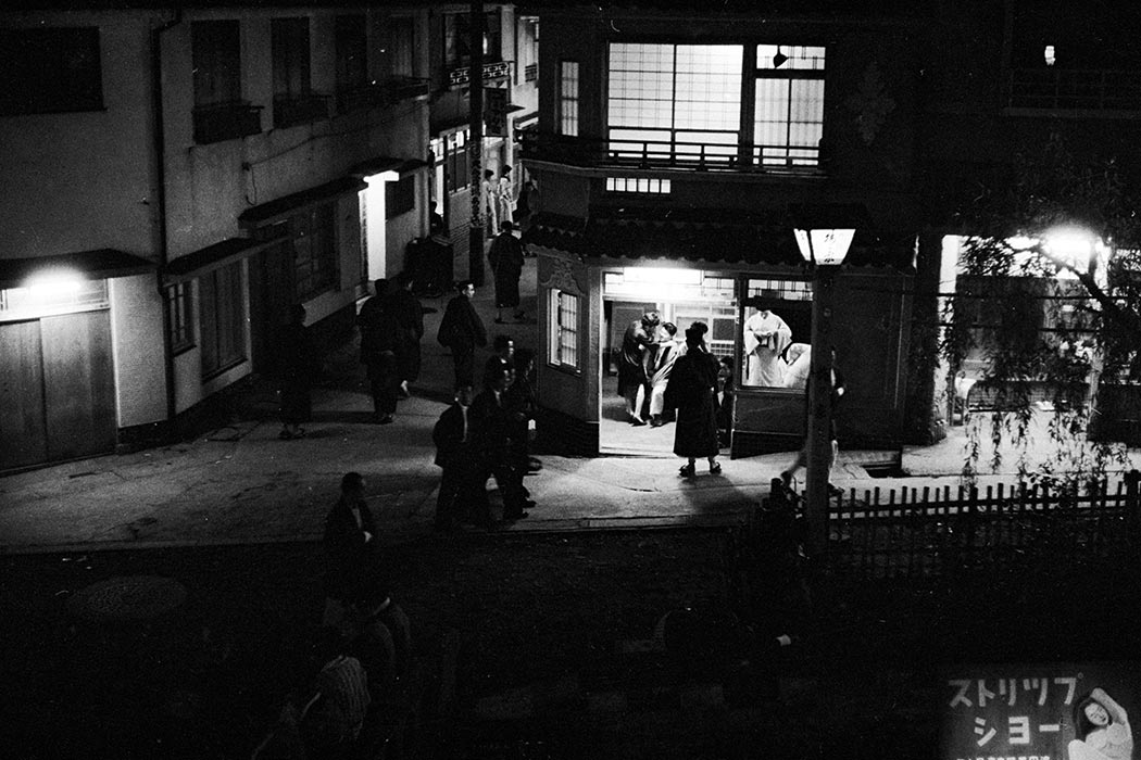 circa 1955: Women loiter in the doorways of nightclubs in Yoshiwara, the red light district of Tokyo, while prospective clients wander past or stop to look. (Photo by Orlando /Three Lions/Getty Images)