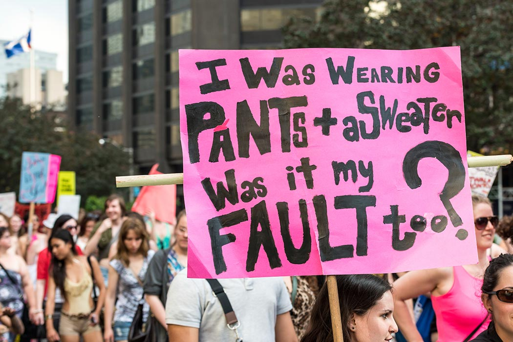 "Toronto, Canada - May 25, 2012: A protest sign reading ""I was wearing pants + a sweater, was it my fault too?"" Taken during ""Slut Walk 2012"", a protest event about sexual assault and victims' rights, among other related issues."