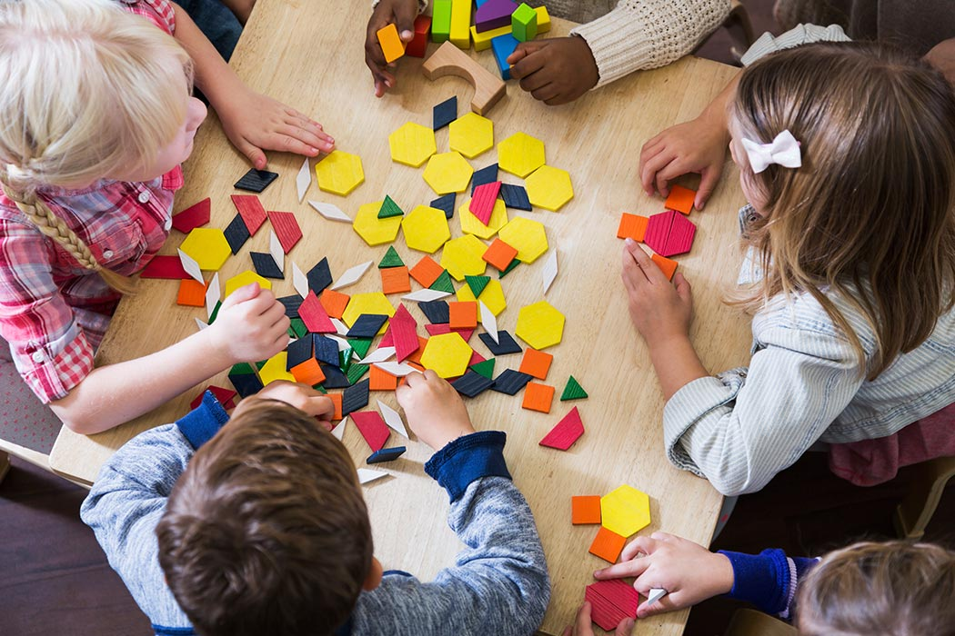 Children at preschool playing with colorful shapes.