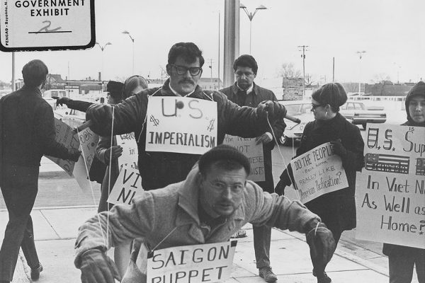 """Protesters carry signs and act out """"Saigon Puppet"""" demonstration in front of Wichita City Building."""