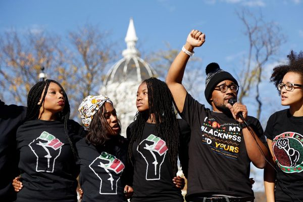 Concerned Student 1950, led by University of Missouri graduate student Jonathan Butler, second from right, speaks following the announcement that University of Missouri System President Tim Wolfe would resign Monday, Nov. 9, 2015, in Columbia, Mo. Wolfe resigned Monday with the football team and others on campus in open revolt over his handling of racial tensions at the school. (Sarah Bell/Missourian via AP)
