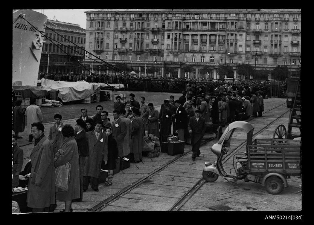Photo credit: Migrants standing in line to embark CASTEL VERDE at a wharf in Trieste, Italy before departing for Australia, 1953-1954. (Australian National Maritime Museum)