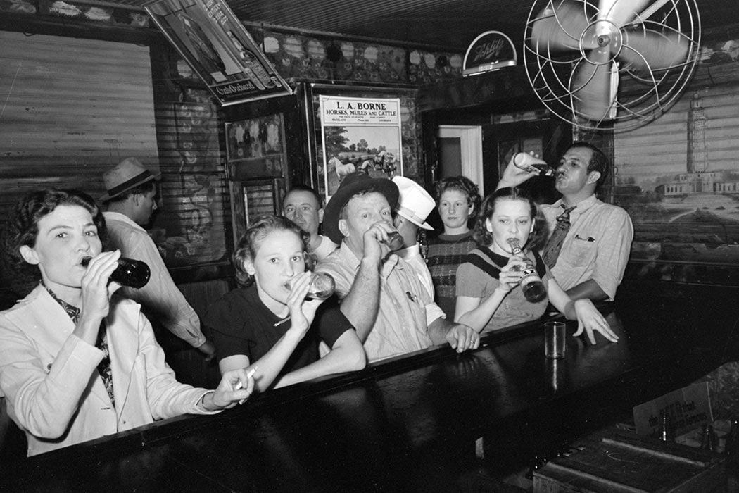 Men and women drinking beer at a pre-prohibition bar in Raceland, Louisiana, September 1938.