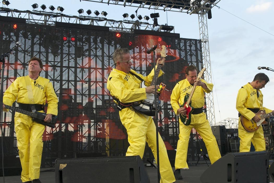 Devo onstage in their trademark bright yellow costumes.