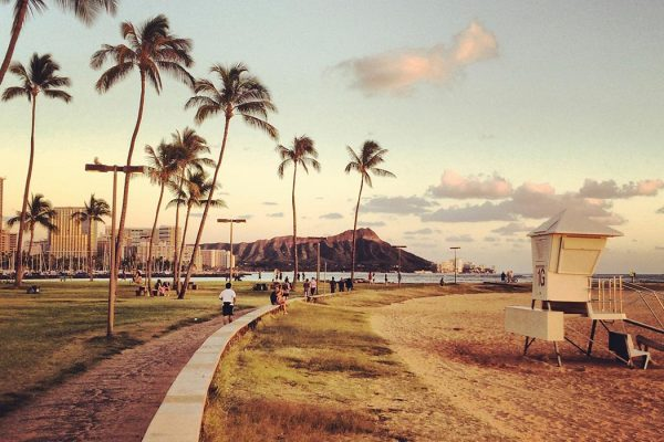 People enjoying their evening on a beach on Honolulu, Hawaii.