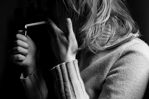 Woman lighting a cigarette.