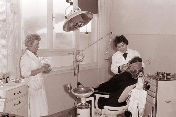 Female dentist with patient, 1960.