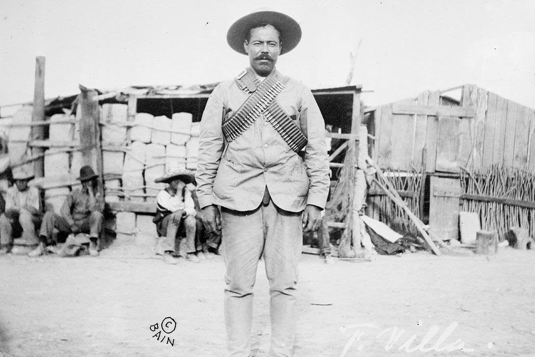 "Francisco ""Pancho"" Villa (1877–1923), Mexican revolutionary general, wearing bandoliers in front of an insurgent camp. By Bain News Service, publisher."