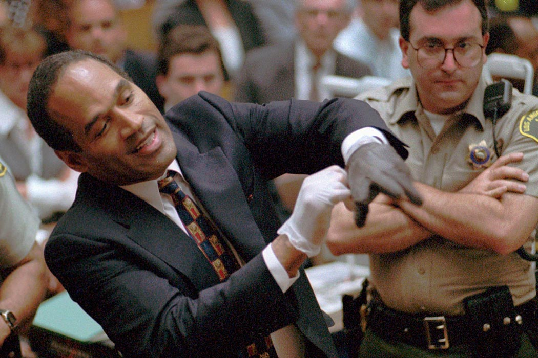 "In this June 15, 1995, file photo, murder defendant, O.J. Simpson grimaces as he tries on one of the leather gloves prosecutors say he wore the night his ex-wife Nicole Brown Simpson and Ron Goldman were murdered, during the Simpson double-murder trial in Los Angeles. A lawyer for O.J. Simpson in Las Vegas says the imprisoned former football star isn't happy with portrayals he's seen in ads and interviews about a cable TV series focusing on his 1995 murder acquittal in Los Angeles. Simpson won't be able to see the show, ""The People v. O.J. Simpson,"" as Nevada prisons don't carry the FX network, which debuts the 10-part show on Tuesday, Feb. 2, 2016. (Sam Mircovich via AP, Pool, File)"