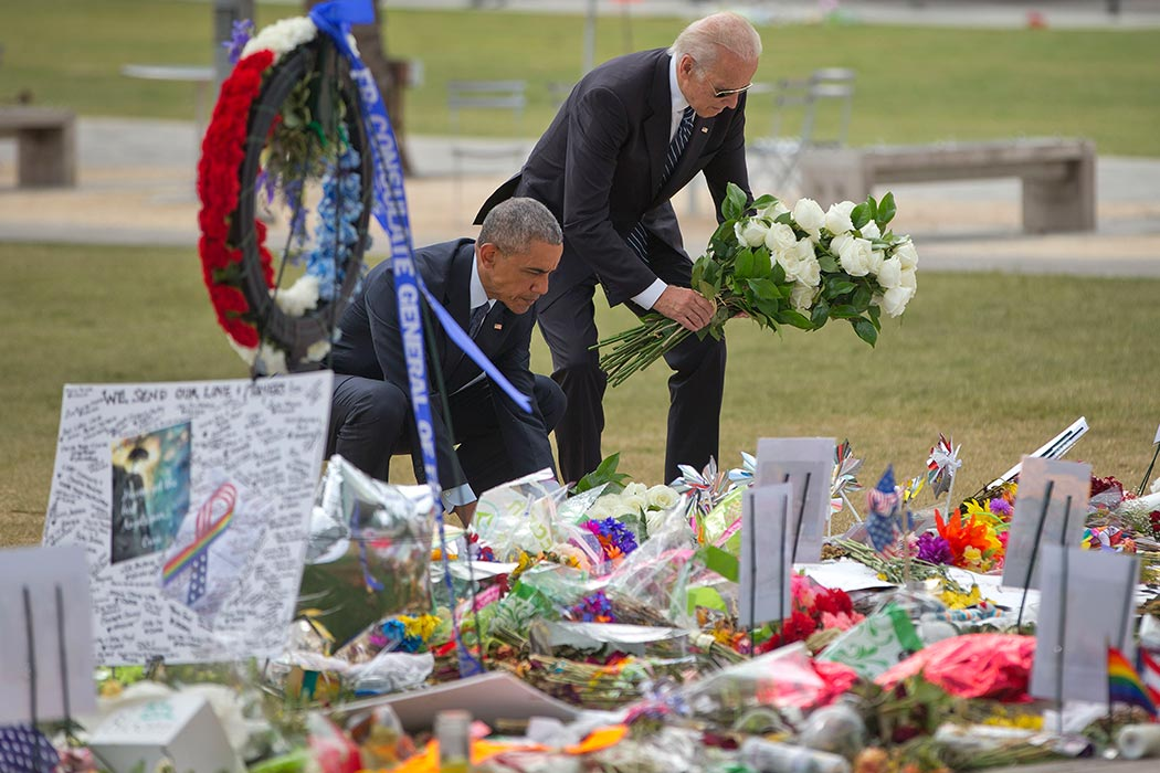 President Barack Obama with Vice President Joe Biden place flowers down during their visit to a memorial to the victims of the Pulse nightclub shooting, Thursday, June 16, 2016 in Orlando, Fla. Offering sympathy but no easy answers, Obama came to Orlando to try to console those mourning the deadliest shooting in modern U.S history. (AP Photo/Pablo Martinez Monsivais)