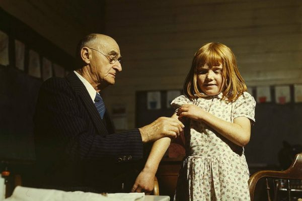 A doctor giving a young girl a vaccination