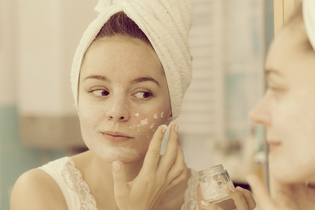Photograph: a woman applying facial cosmetic product.