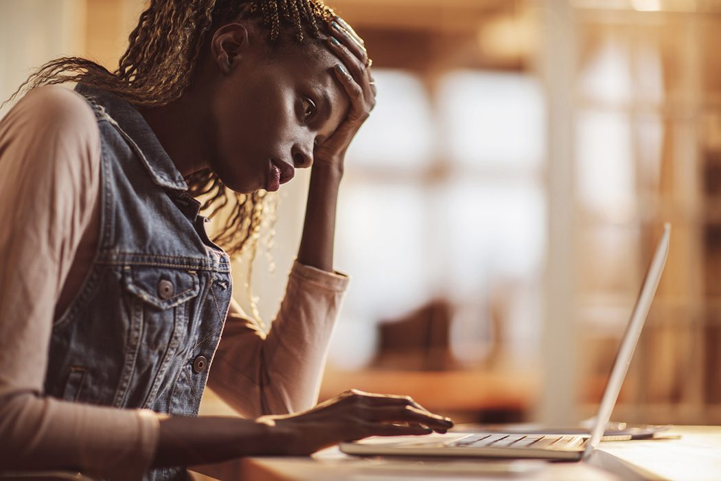 young woman distressed at a laptop
