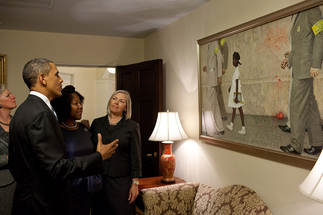 "Photograph: President Barack Obama, Ruby Bridges,  and representatives of the Norman Rockwell Museum view Rockwell's  ""The Problem We All Live With,""  hanging in a West Wing hallway near the Oval Office, July 15, 2011.  Ruby Bridges is the girl in the painting. (Official White House Photo by Pete Souza) This official White House photograph is being made available only for publication by news organizations and/or for personal use printing by the subject(s) of the photograph. The photograph may not be manipulated in any way and may not be used in commercial or political materials, advertisements, emails, products, promotions that in any way suggests approval or endorsement of the President, the First Family, or the White House.   Source: https://flic.kr/p/a41wAb"