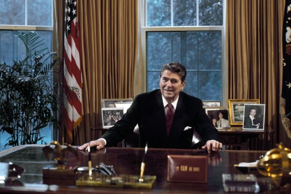 President Ronald Reagan at his desk in the Oval Office.