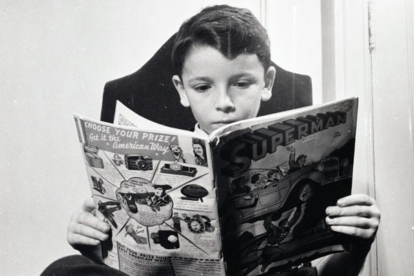 Refugee child reading Superman