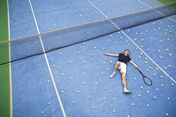 Male tennis player lying on ground