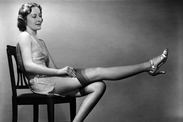 Woman sitting on chair, putting on stockings
