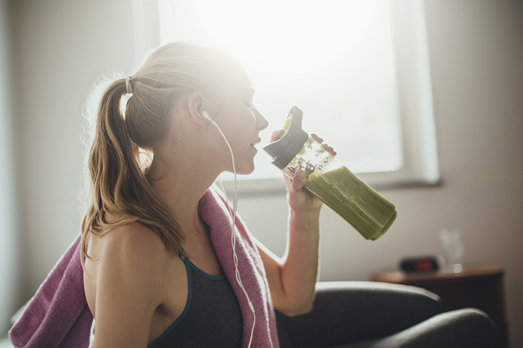 Young woman drinking a green smoothie after training