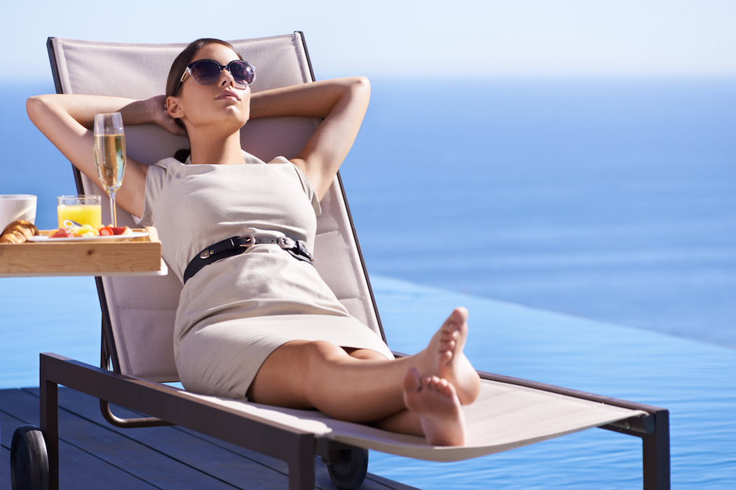 A posh young woman reclining on a deck chair with her hands behind her head