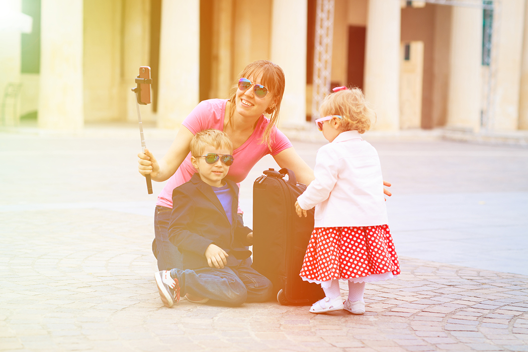 mother and kids taking selfie stick picture in Europe