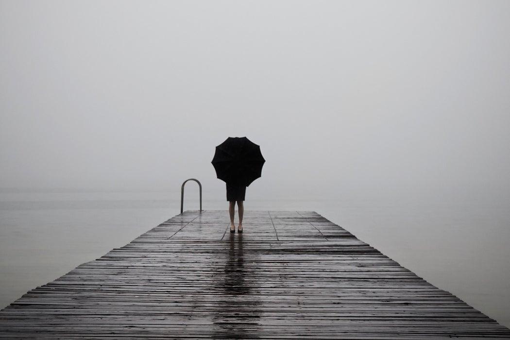 elegant woman dressed in black hiding with umbrella