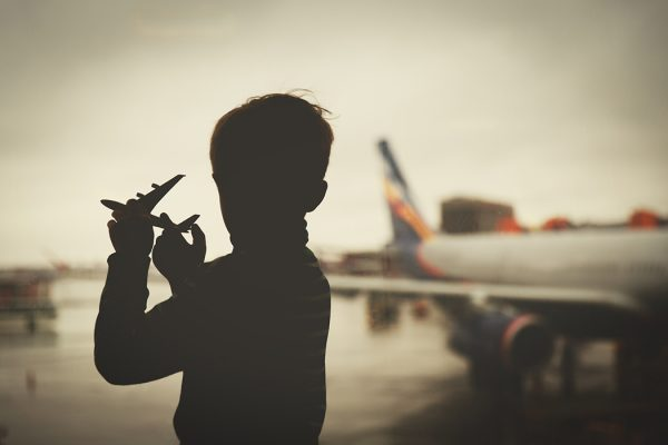 boy playing with toy plane while waiting in airport