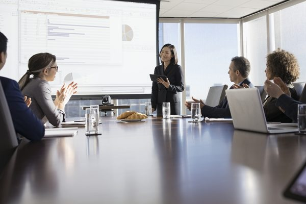 Business people clapping for businesswoman leading presentation in conference room