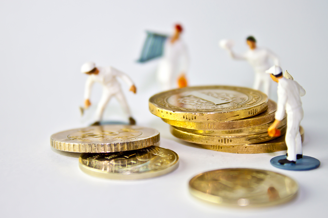 miniature people standing on around a stack of coins