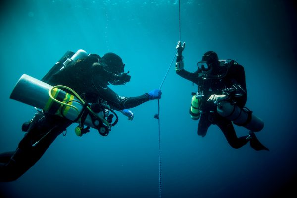 Underwater view of two technical divers using rebreathers device to locate shipwreck, Lombok, Indonesia