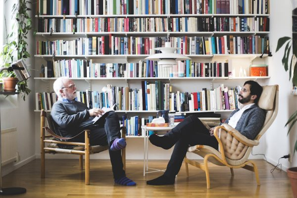Therapist communicating with man while sitting by book shelf at home office