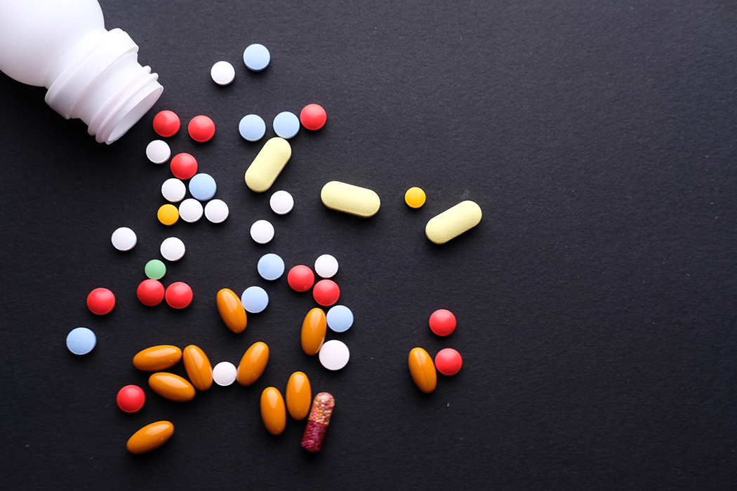 Many pills and tablets with bottle isolated on black background.