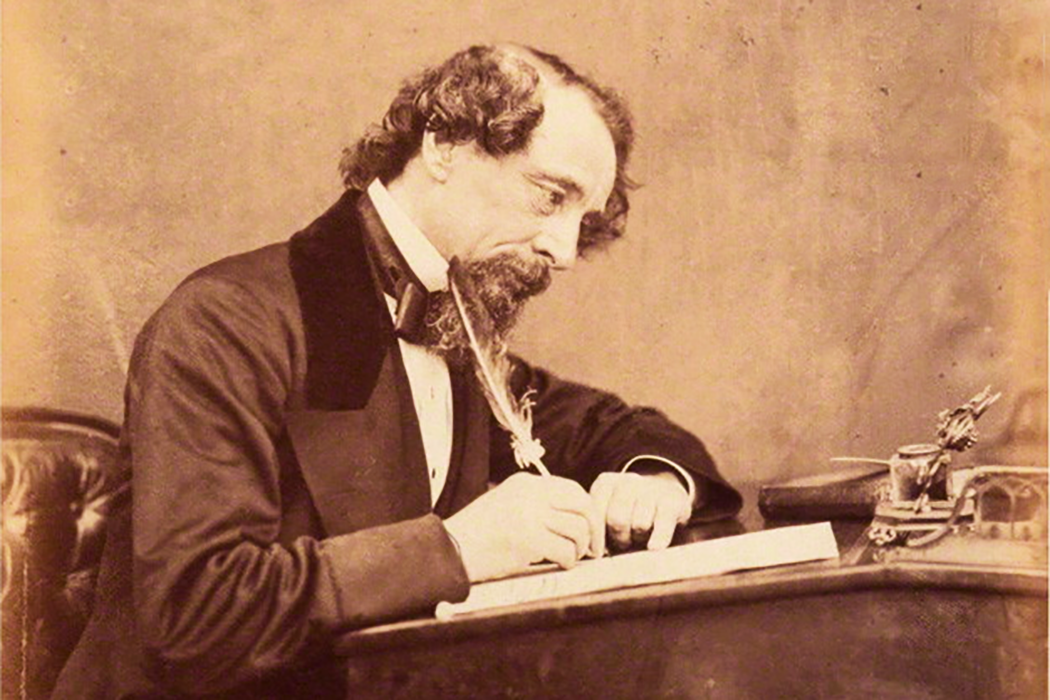 Charles Dickens in 1858 writing at a desk
