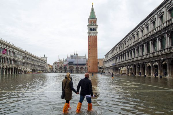 Venice, Italy with flooding and tourists walking in high water