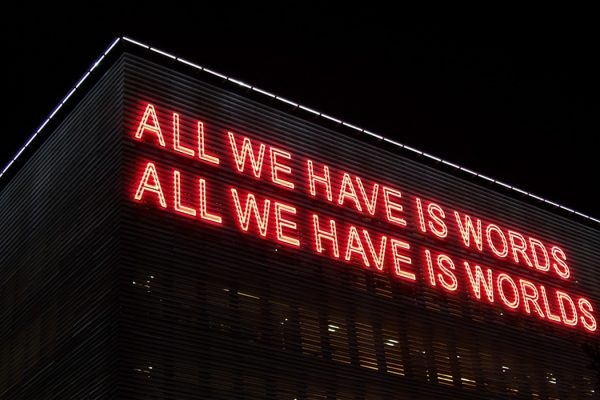 "Neon text on the side of a building reads ""All we have is words, all we have is worlds."""