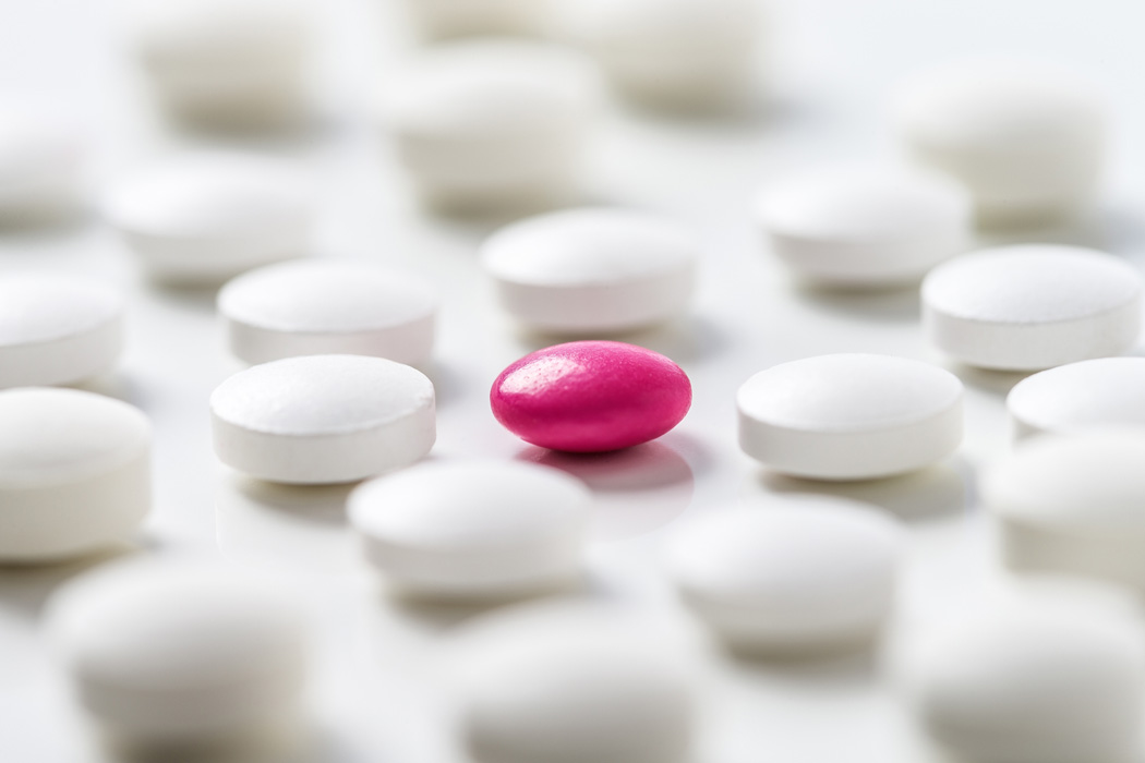 A pink pill on a table amongst white pills.
