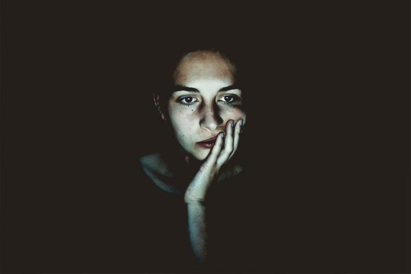 A woman's face lit up in a dark room