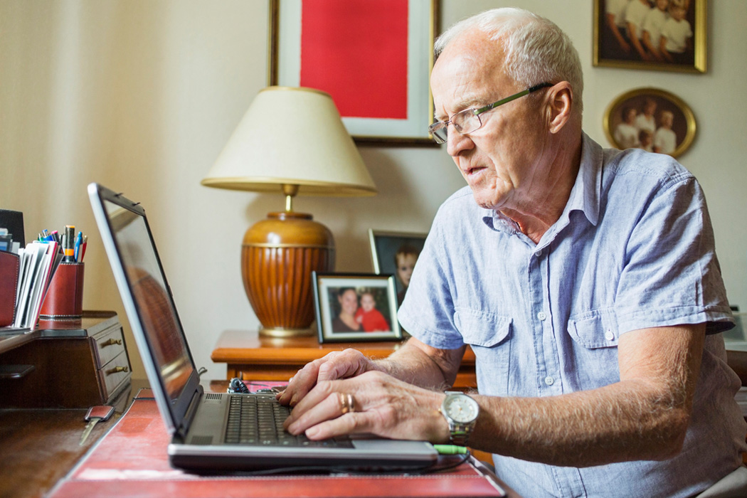 An elderly man typing on a laptop