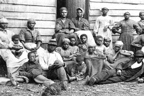 A group of slaves gathered outside a building at the Foller Plantation in Cumberland Landing, Pamunkey Run, Virginia, May, 1862.