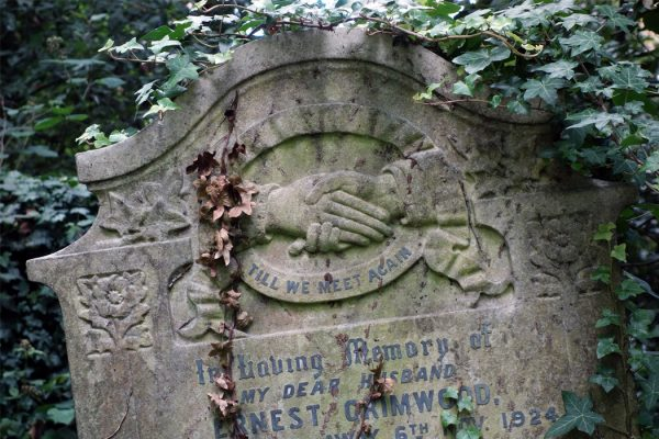A headstone featuring clasped hands