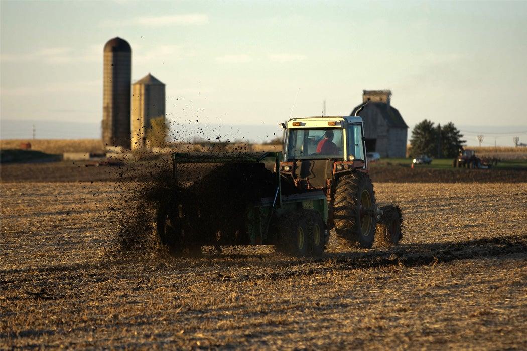 A tractor spreads biosolids in a field