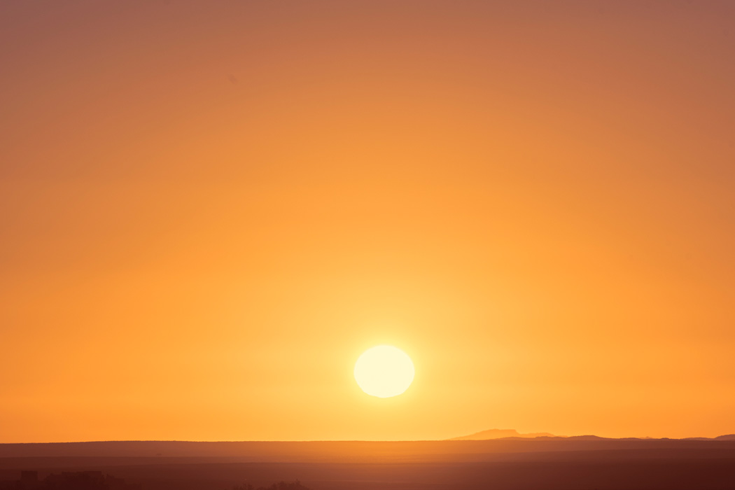 The sun setting in a cloudless sky