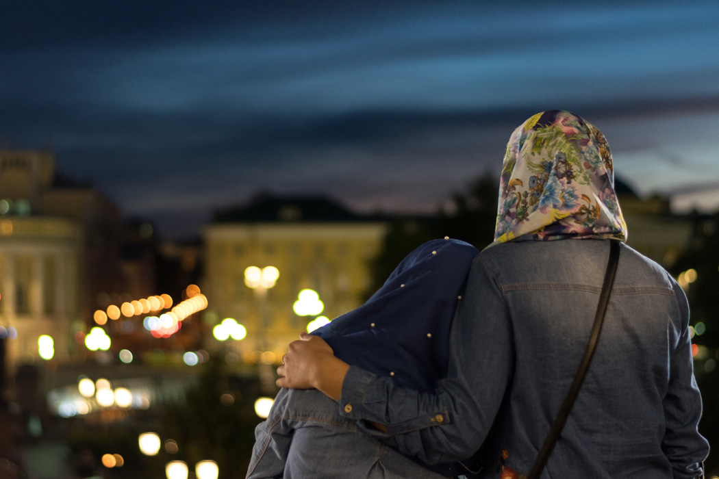 Two muslim women looking out over a city.