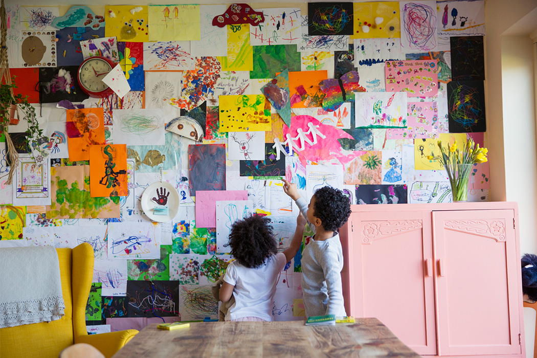 Two children looking at artwork hung on the wall