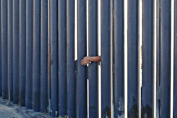 A woman's hand against a border wall