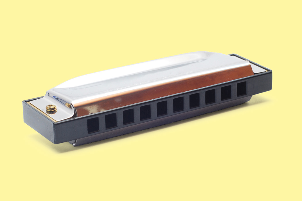 A harmonica against a yellow background